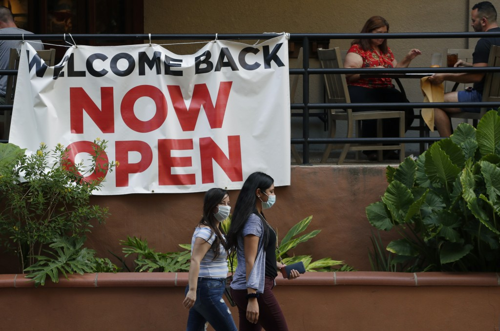 FILE - In this May 27, 2020, file photo, visitors to the River Walk pass a restaurant that has reopened in San Antonio. Coronavirus cases are rising i...