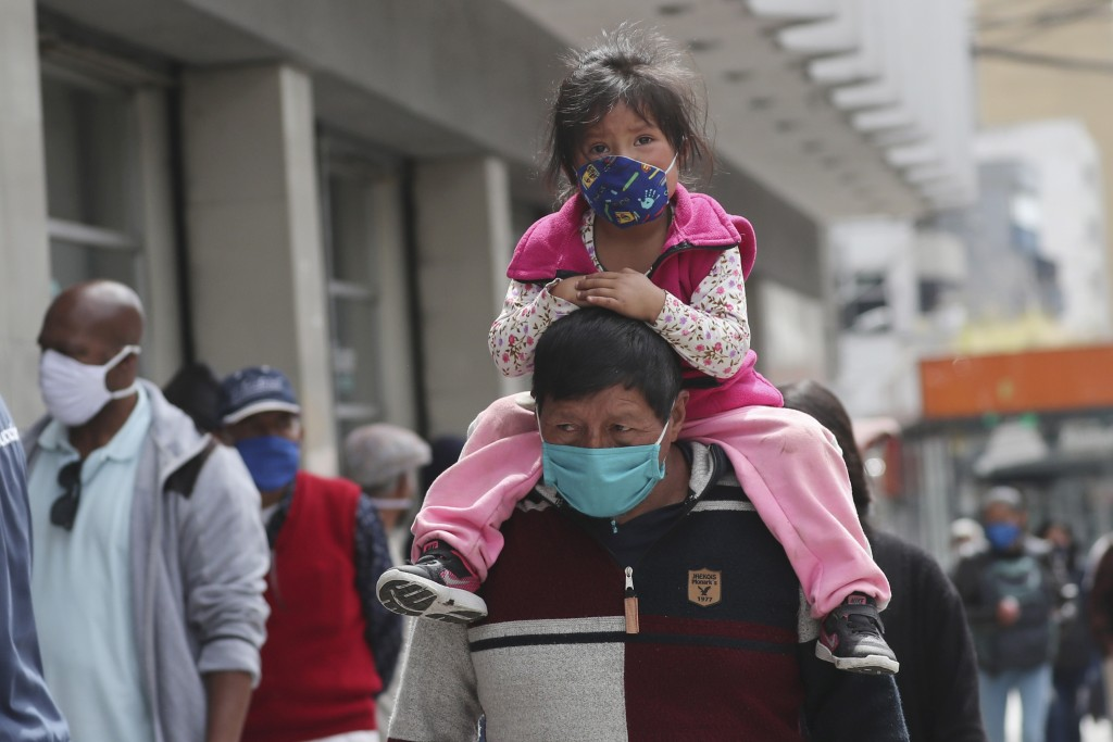 A child, wearing a protective face mask as a mandatory measure to help curb the spread of the new coronavirus, rides piggyback through a crowded downt...