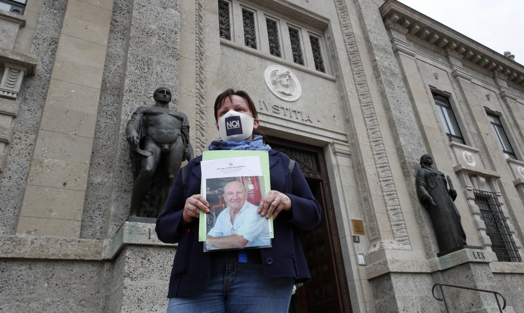 Laura Silvestri holds up a photograph of her father Giuseppe, a COVID-19 victim, has she stands in front of Bergamo's court, Italy, Wednesday, June 10...