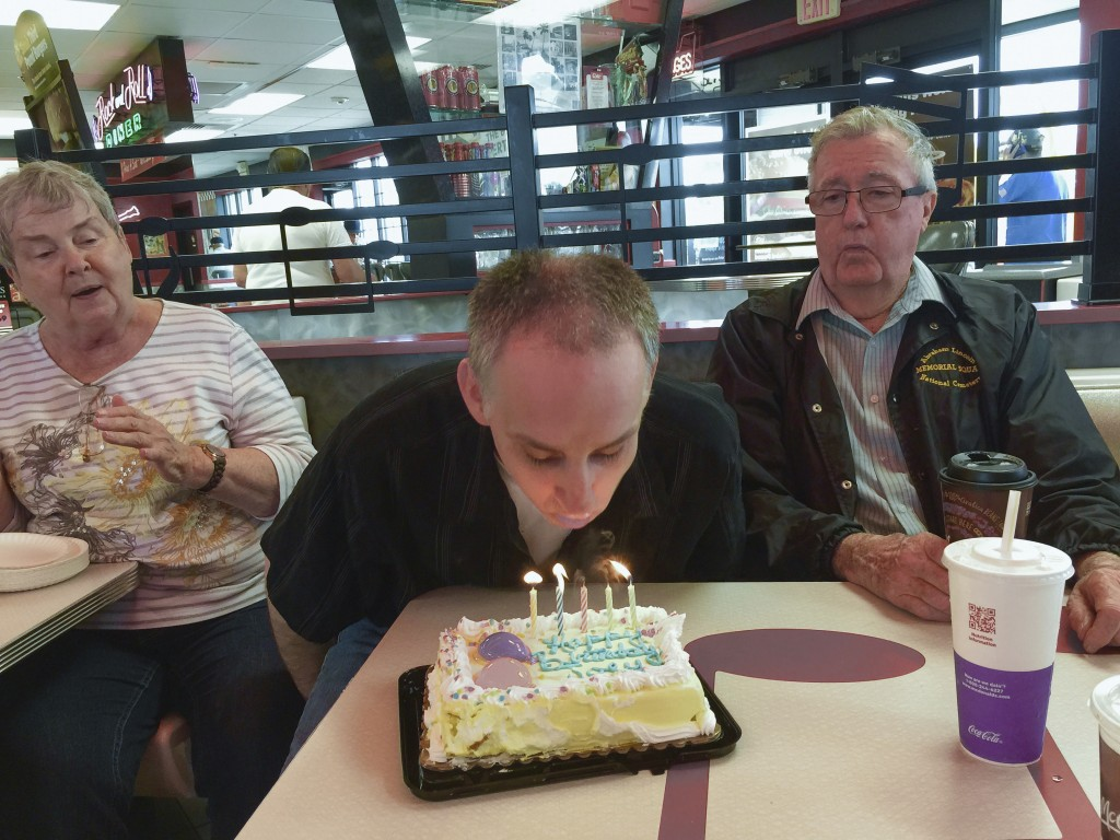 This 2015 photo provided by the family shows Joe Sullivan, of the Chicago-area, and his parents celebrating his birthday at a restaurant. (Family phot...