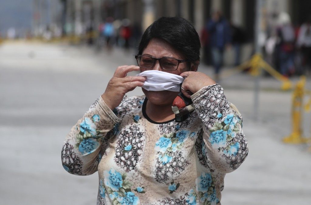 A woman hurriedly places a protective face mask over her mouth and nose to avoid a $100.00 US dollar fine, as wearing a face mask in public is mandato...