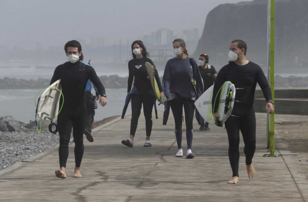 Wearing a face masks as a precaution amid the spread of the new coronavirus, surfers arrive at the reopened Waikiki beach in the Miraflores district o...