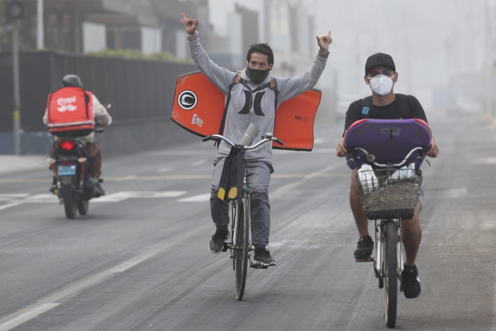 Wearing face masks as a precaution amid the spread of the new coronavirus, surfers cycle to Waikiki Beach in the Miraflores district of Lima, Peru, Th...