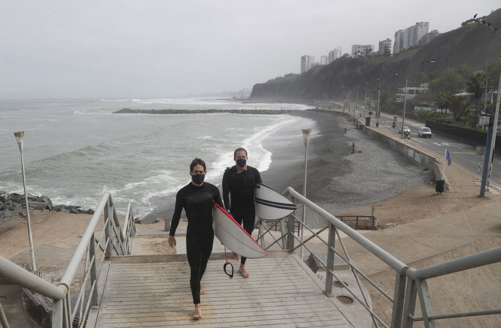 Wearing face masks as a precaution amid the spread of the new coronavirus, surfers leave the reopened Waikiki beach in the Miraflores district of Lima...