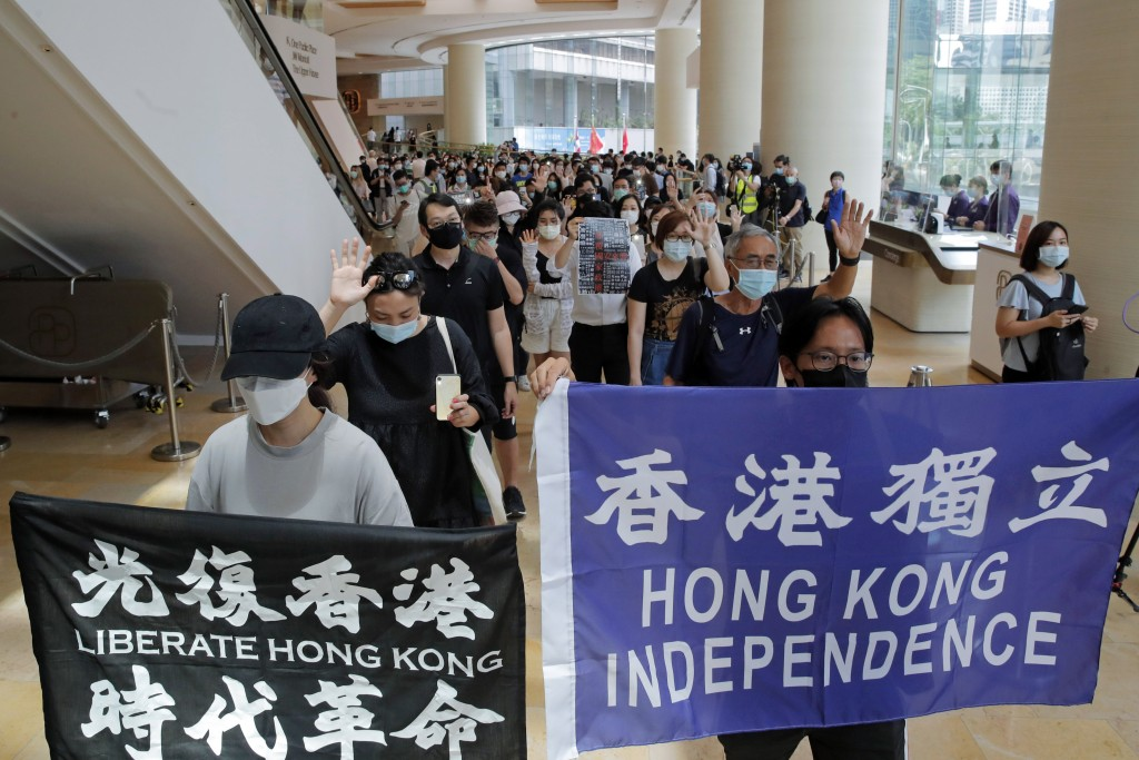 Protesters hold flags in a shopping mall during a protest in Hong Kong, Friday, June 12, 2020. Protesters in Hong Kong got its government to withdraw ...