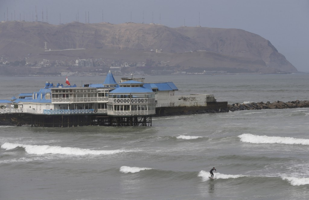 A surfer rides a small wave in the Pacific Ocean along the coast of Lima, Peru, Thursday, June 11, 2020. The emblematic surfers who dot Peru's coastli...