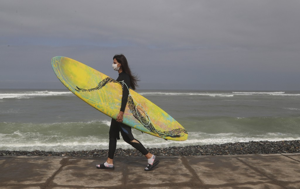 Wearing a face mask as a precaution amid the spread of the new coronavirus, a surfer walks to Waikiki beach in the Miraflores district of Lima, Peru, ...