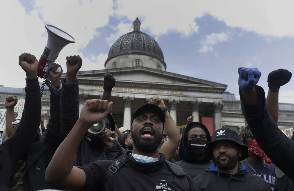 Members of Black Lives Matter movement chant slogans during a protest at Trafalgar Square in central London, Saturday, June 13, 2020. British police h...