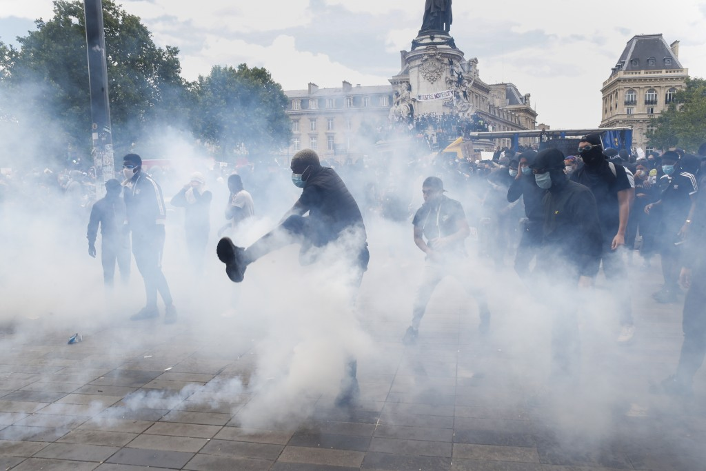A man kicks a tear gas canister during a march against police brutality and racism in Paris, France, Saturday, June 13, 2020, organized by supporters ...