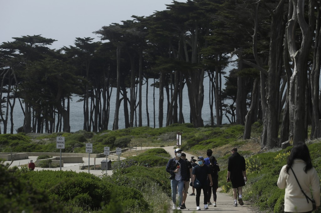 FILE - In this April 24, 2020, file photo people wear masks amid the coronavirus pandemic while walking on a path at Land's End in San Francisco. Lawm...