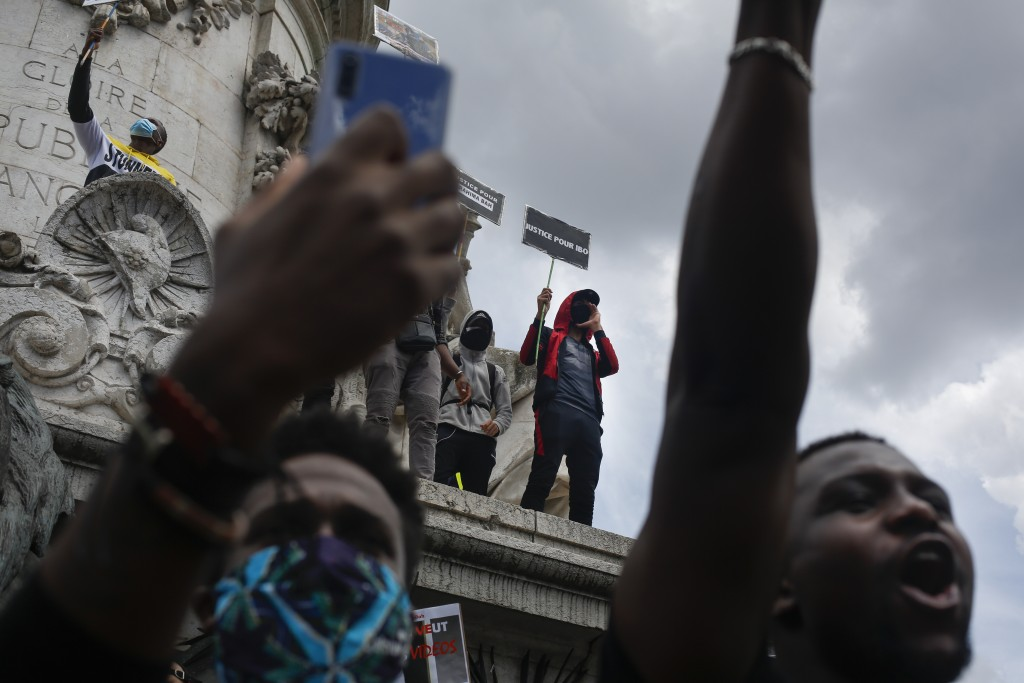 People gather at Place de la Republique for march against police brutality and racism in Paris, France, Saturday, June 13, 2020, organized by supporte...