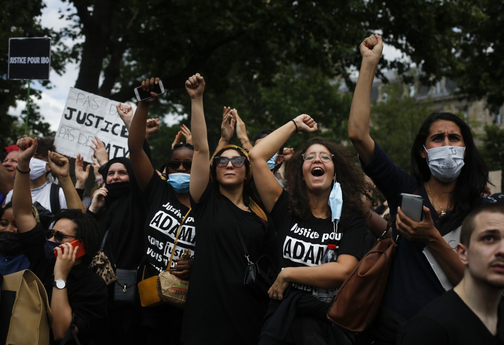 Demonstrators clench fists as thousands of people take part in a march against police brutality and racism in Paris, France, Saturday, June 13, 2020, ...