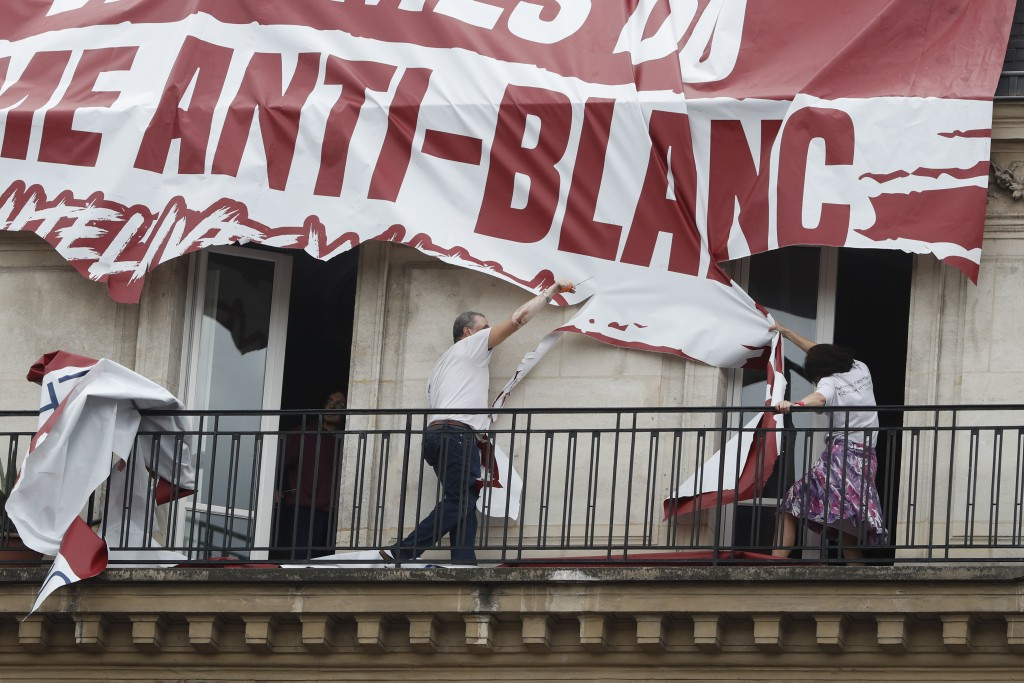 Residents of a building cut up a banner which was lowered from the roof of his building by far-right protestors with the Identitarian nationalist Fren...
