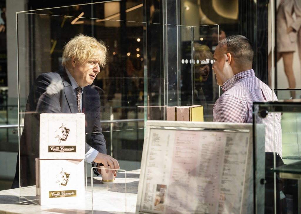Britain's Prime Minister Boris Johnson speaks with Freddy Staple, Operation Manager of Caffe Concerto, right, in Westfield Stratford shopping centre i...