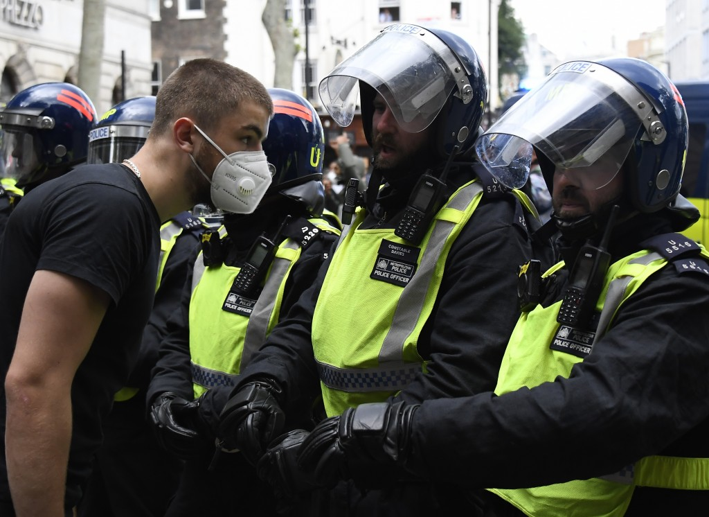A member of Black Lives Matter movement, left, comfronts British police officers in riot gear trying to contain a protest at Trafalgar Square in centr...
