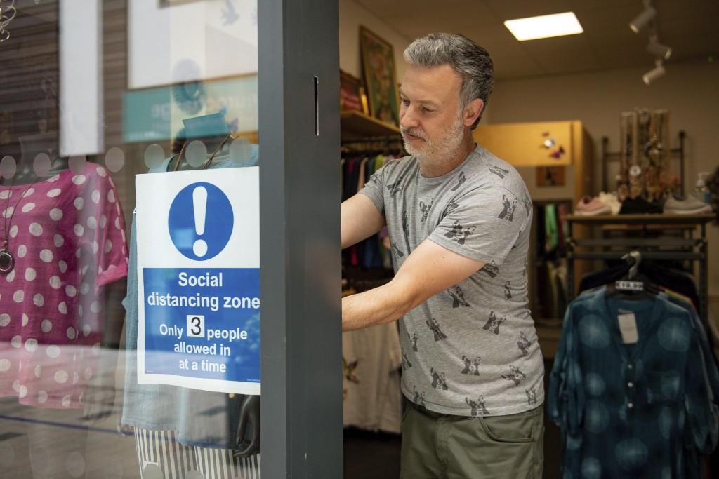Retailer Clive Williams installs a sign in the window of his Pop Up Clothing Company store, in Stratford-upon-Avon, Warwickshire, England, Sunday, Jun...