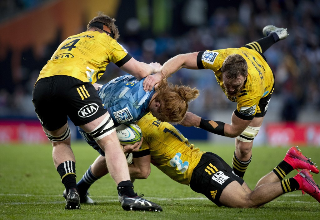 Auckland Blues player Tom Robinson, in blue, is tackled by the defence during the Super Rugby Aotearoa rugby match between the Blues and the Hurricane...