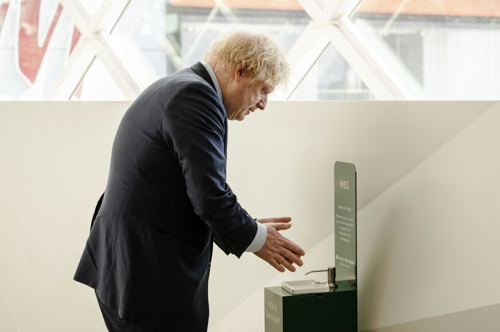 Britain's Prime Minister Boris Johnson visits a shop in Westfield Stratford shopping centre in east London, Sunday June 14, 2020, to see the preparati...