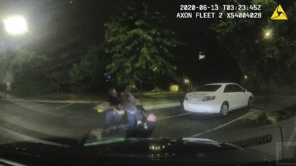 This screen grab taken from dashboard camera video provided by the Atlanta Police Department shows Rayshard Brooks, center, struggling with Officers G...