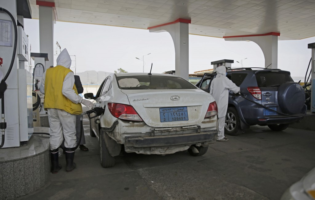 Yemeni attendants wearing personal protective equipment pump fuel at a petrol station amid fuel shortages in Sanaa, Yemen, Monday, June 15, 2020. (AP ...