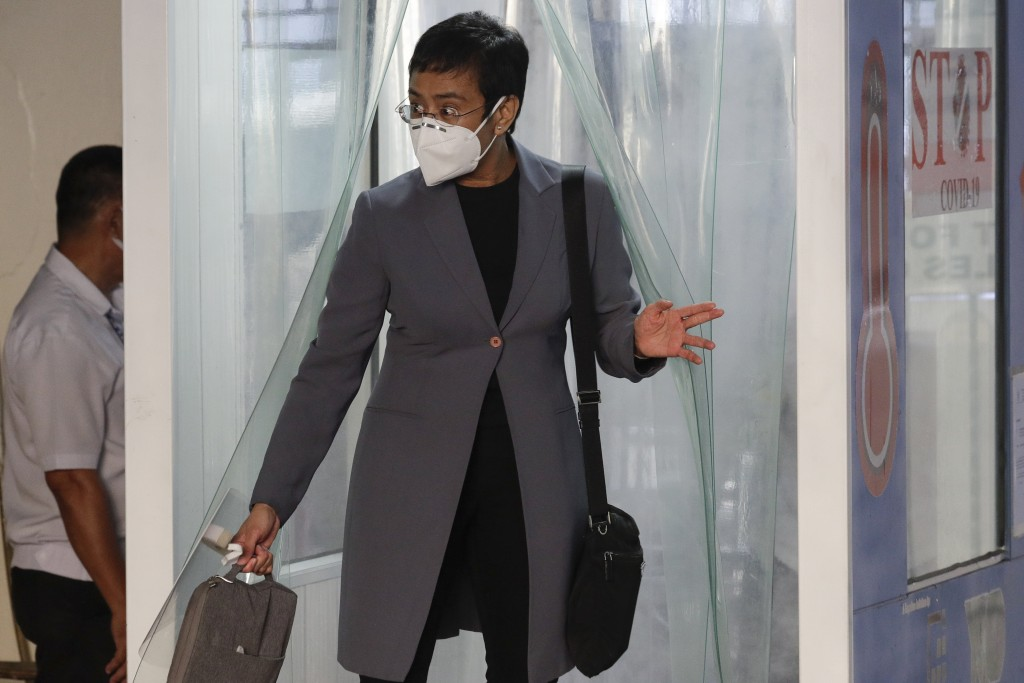 Rappler CEO and Executive Editor Maria Ressa, wearing a protective mask, exits a disinfection area before attending a court hearing at Manila Regional...