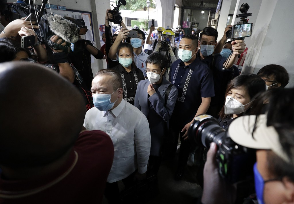 Rappler CEO and Executive Editor Maria Ressa, center, is escorted as she arrives to attend a court hearing at Manila Regional Trial Court, Philippines...