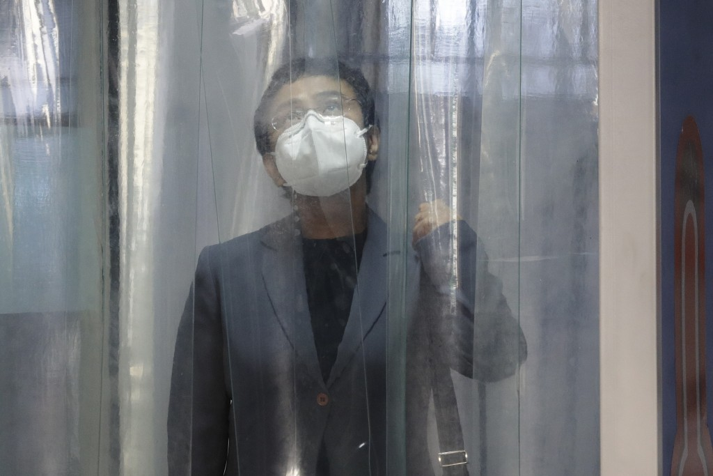 Rappler CEO and Executive Editor Maria Ressa, wearing a protective mask, enters a disinfection area before attending a court hearing at Manila Regiona...