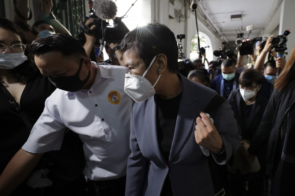 Rappler CEO and Executive Editor Maria Ressa, front right, wearing a protective mask, is escorted as she arrives to attend a court hearing at Manila R...