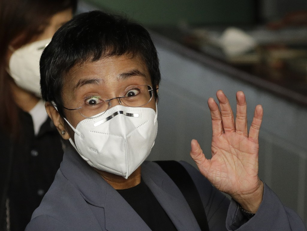 Rappler CEO and Executive Editor Maria Ressa, wearing a protective mask, waves to the media before attending a court hearing at Manila Regional Trial ...