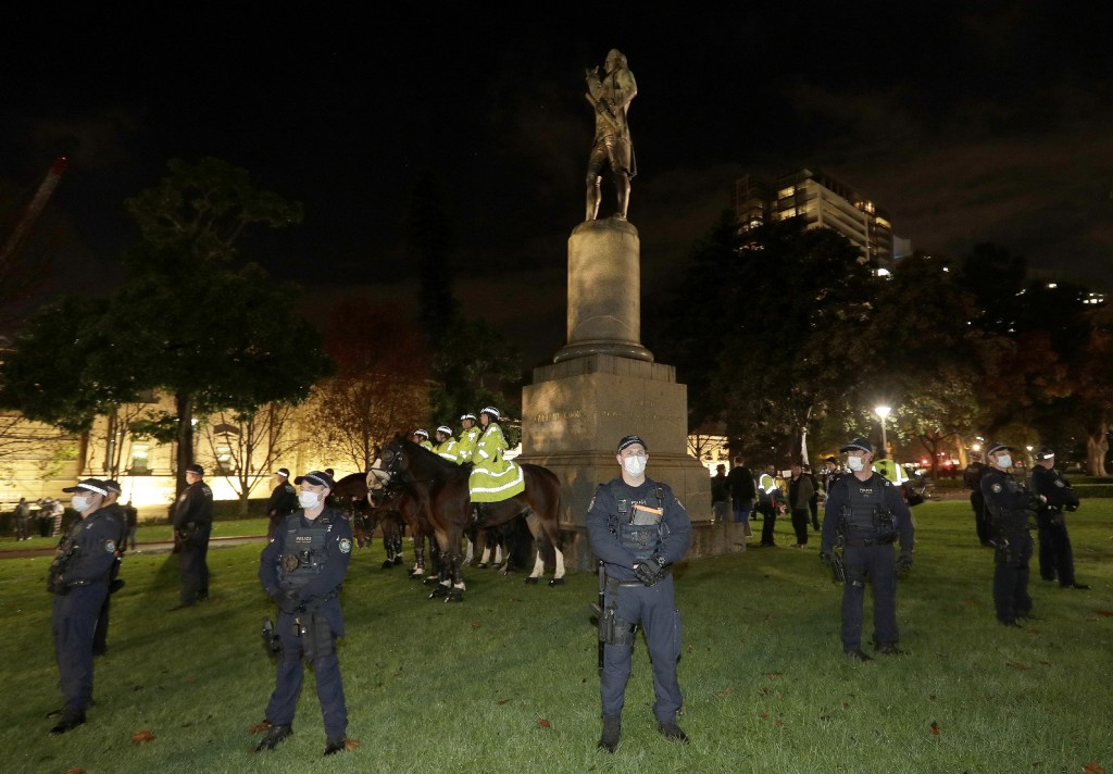 FILE - In this June 12, 2020, file photo, police guard a statue of British explorer James Cook as protesters gather in Sydney, to support U.S. protest...