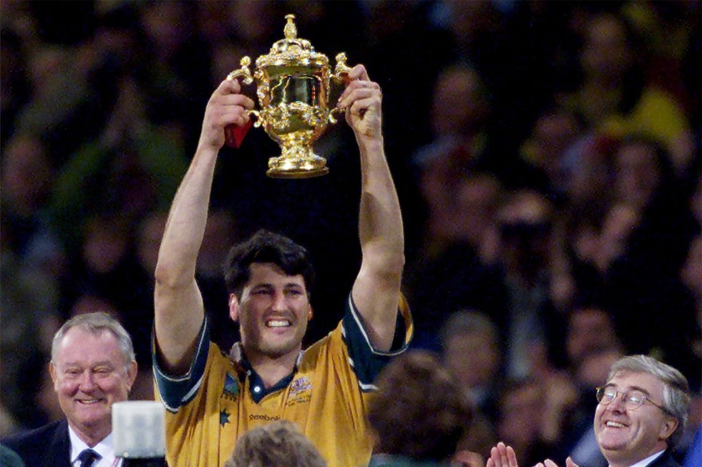 FILE - In this Nov. 6, 1999, file photo, Australia's rugby captain John Eales holds the trophy aloft at the end of the Rugby World Cup at the Millenni...
