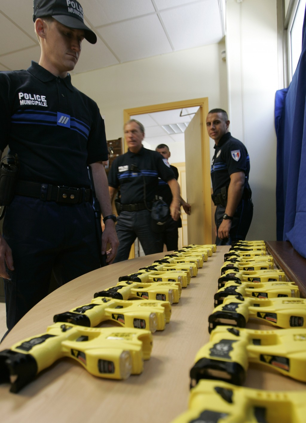 ADDS AN UPDATE FROM THE FRENCH GOVERNMENT - FILE - In this July 10, 2009, file photo, Tasers sit on a table in Nice, southeastern France. France's gov...