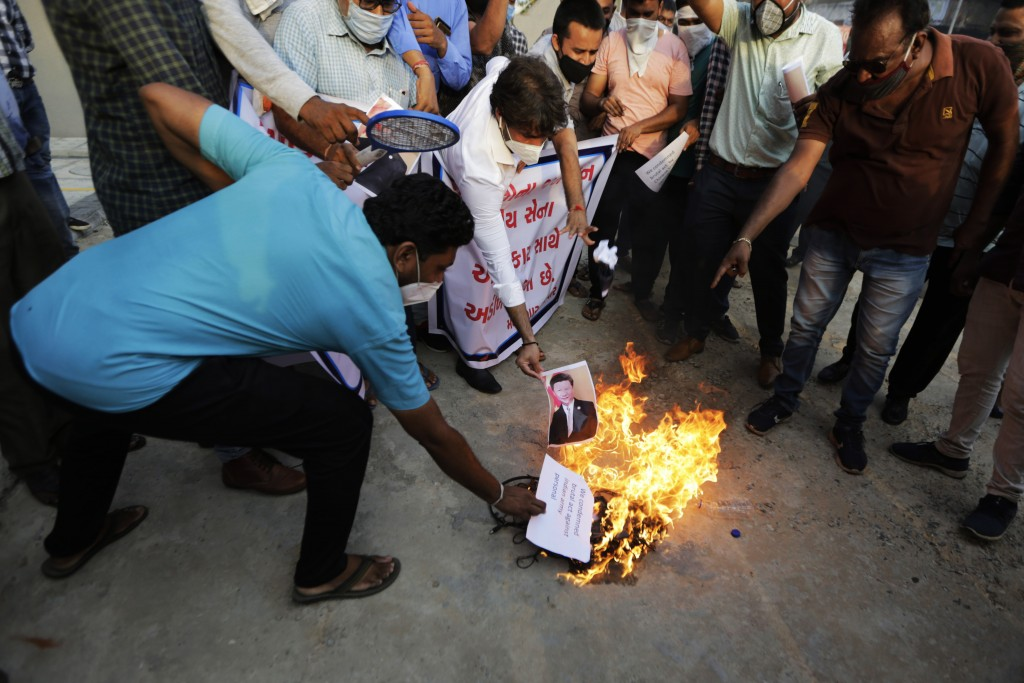 An Indian man burns a photograph of Chinese president Xi Jinping during a protest against China in Ahmedabad, India, Tuesday, June 16, 2020. At least ...