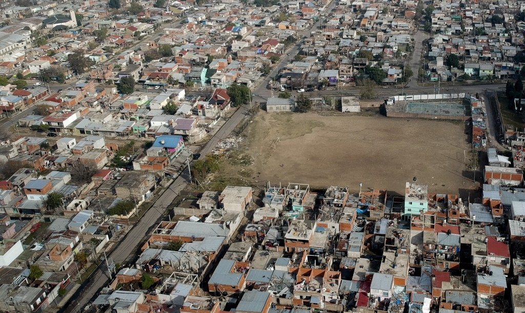 """A soccer field called """"El Potrero,"""" where soccer star Diego Maradona started playing as a kid, is surrounded by homes in the Fiorito slum where he was..."""