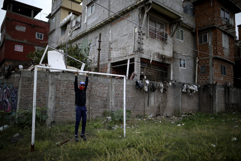 Nicolas Suarez, 16, poses for a photo as he hangs from a soccer goalpost in a soccer field that's closed due to the COVID-19 lockdown in the Fraga nei...