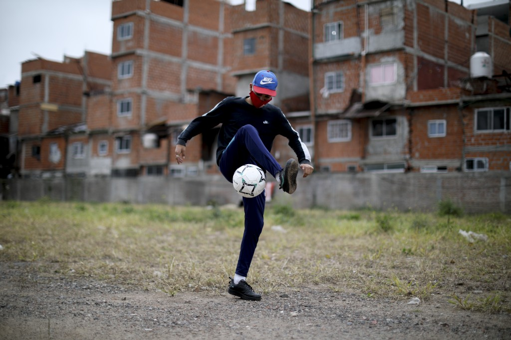 Nicolas Suarez, 16, controls the ball as he poses for a photo on the soccer field of the Fraga neighborhood, empty amid the COVID-19 lockdown to curb ...