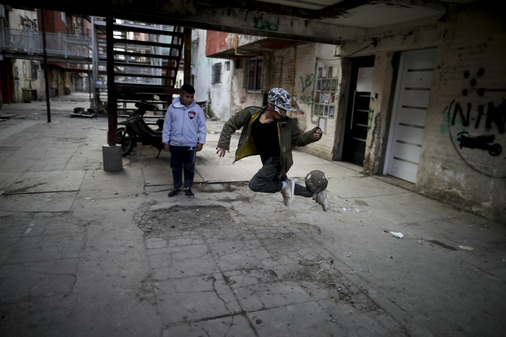 A youth controls a soccer ball outside apartment buildings in the Fuerte Apache neighborhood where soccer star Carlos Tevez played as a youth, while s...