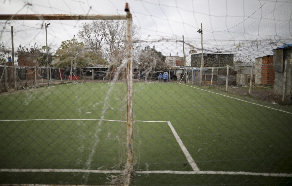 A soccer field is closed as health officials walk along its perimeter in the Villa Azul neighborhood, where officials isolated residents for strick qu...