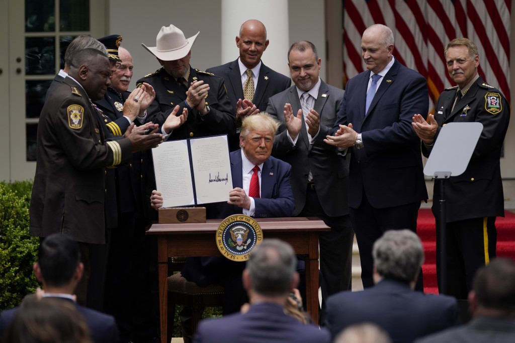President Donald Trump holds up an executive order on police reform after signing it in the Rose Garden of the White House, Tuesday, June 16, 2020, in...