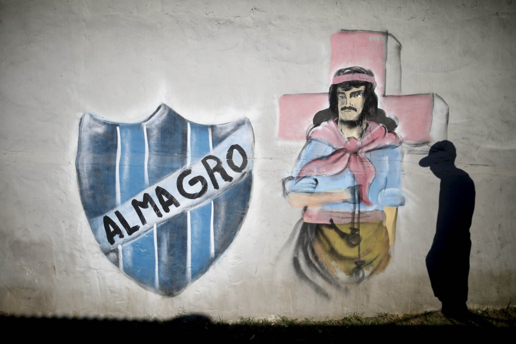 Second division soccer player Tiago Ruiz Diaz poses next to a mural logo of his Almagro soccer club and a painting of folk saint Gauchito Gil in the F...