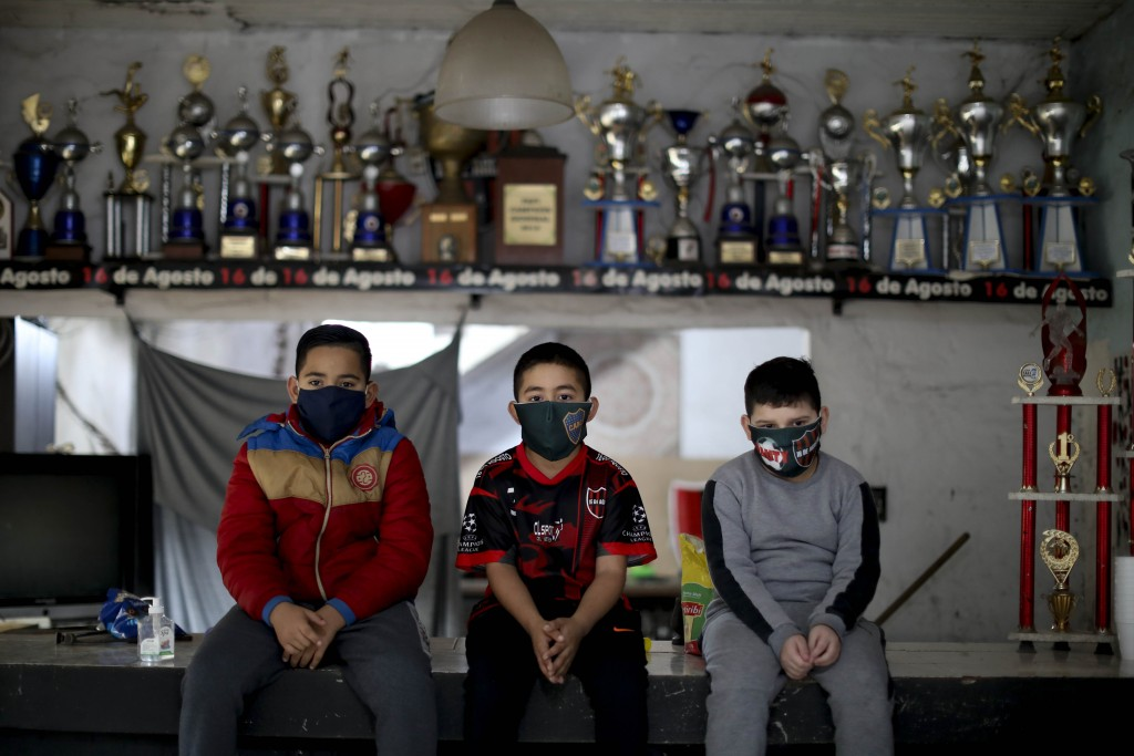 Young soccer players, from left, Daniel Rocaro, Uriel Lopez, and Bauti Fernandez pose for a photo in front of their trophies during an interview at th...