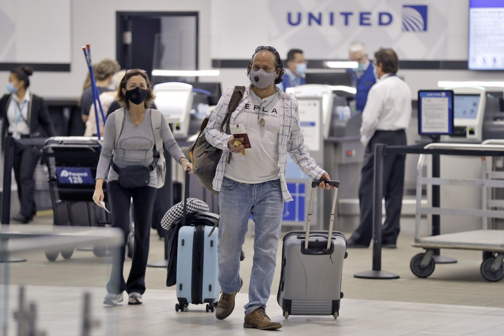 Passengers wearing personal protective face masks leave the United Airline ticket counter after checking in Tuesday, June 16, 2020, at the Tampa Inter...