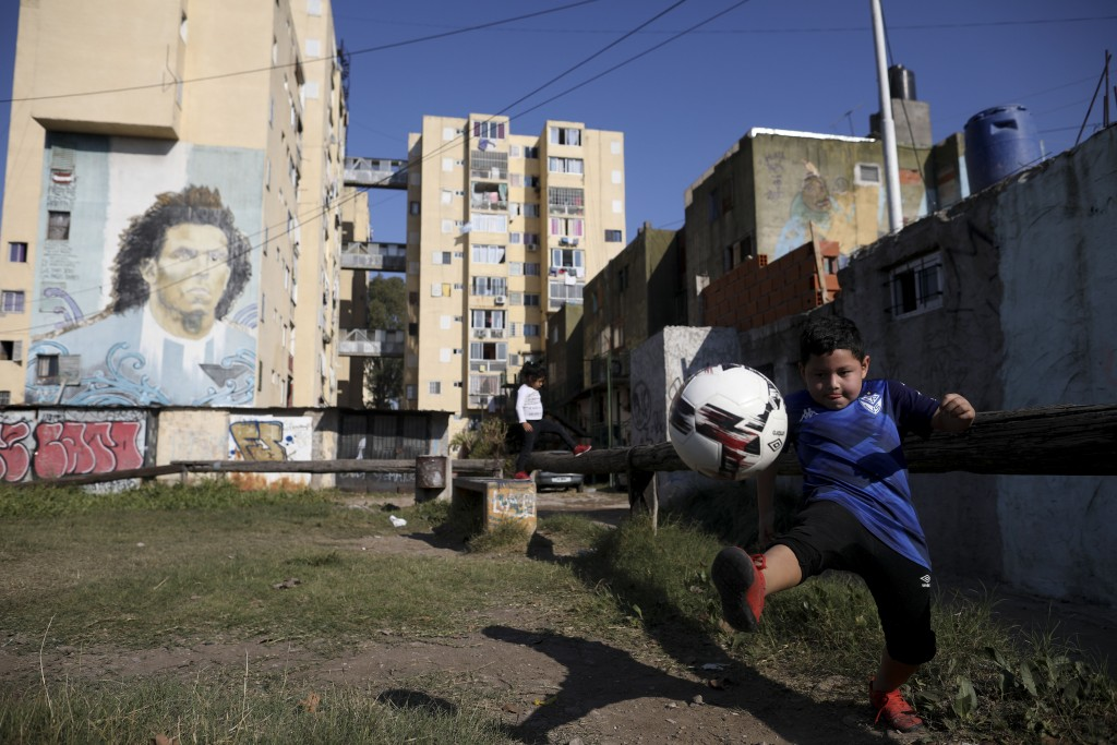 A child plays soccer in a park near a mural of soccer player Carlos Tevez in the Fuerte Apache neighborhood, where Tevez played as a youth in Buenos A...
