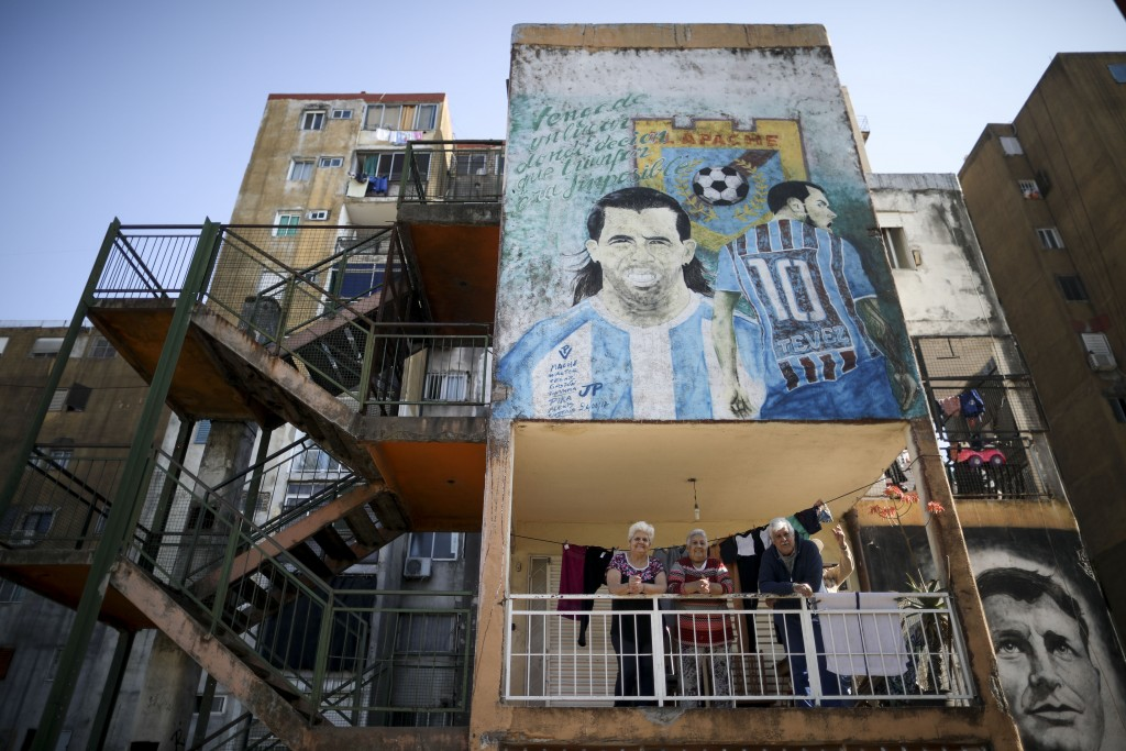 """Residents stand on their balcony below a mural of soccer star Carlos Tevez that reads in Spanish """"I come from a place where they said success was impo..."""