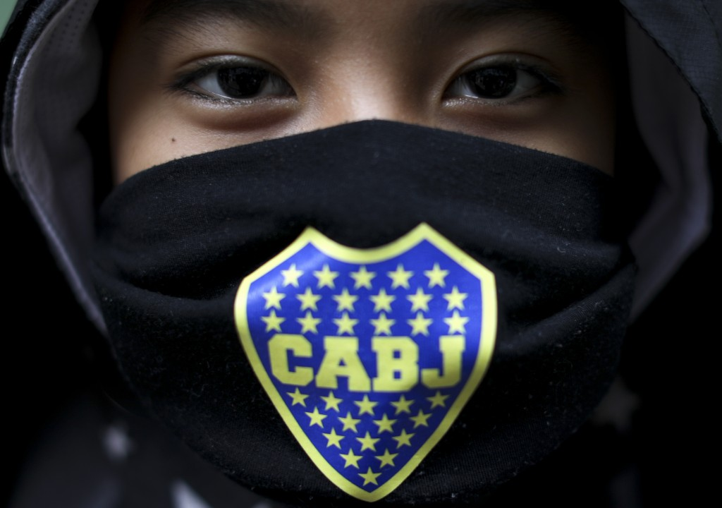 Thiago Laura poses for a photo wearing his Boca Juniors face mask as he waits for food at a soup kitchen in the Fraga neighborhood during the lockdown...