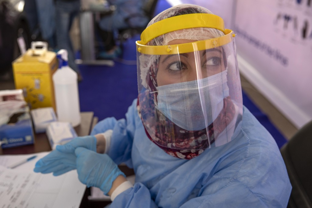 A health worker wearing protective gear prepares to take swab samples from people lining up in their cars to test for the coronavirus at a drive-throu...