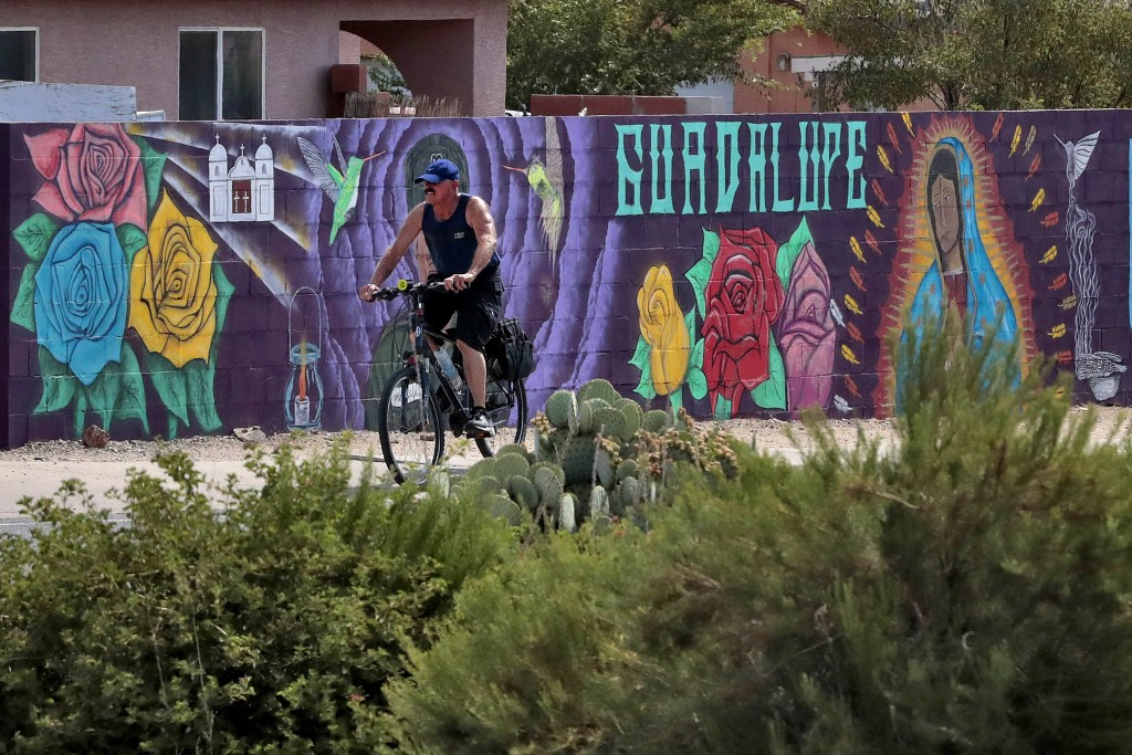 In this Saturday, June 13, 2020, photo, a man cycles past a mural in Guadalupe, Ariz. As the coronavirus spreads deeper across America, it's ravaging ...