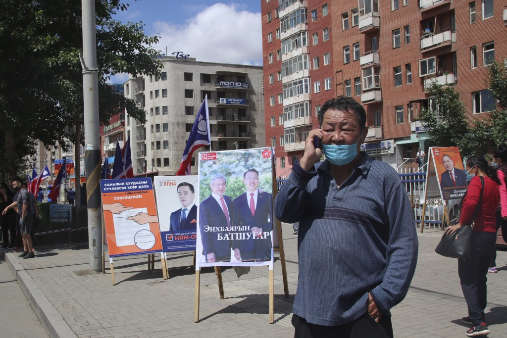 A man wearing a mask and using his phone stands near the election stand of Mongolian People's Revolutionary Party or MPRP featuring ex-president of Mo...