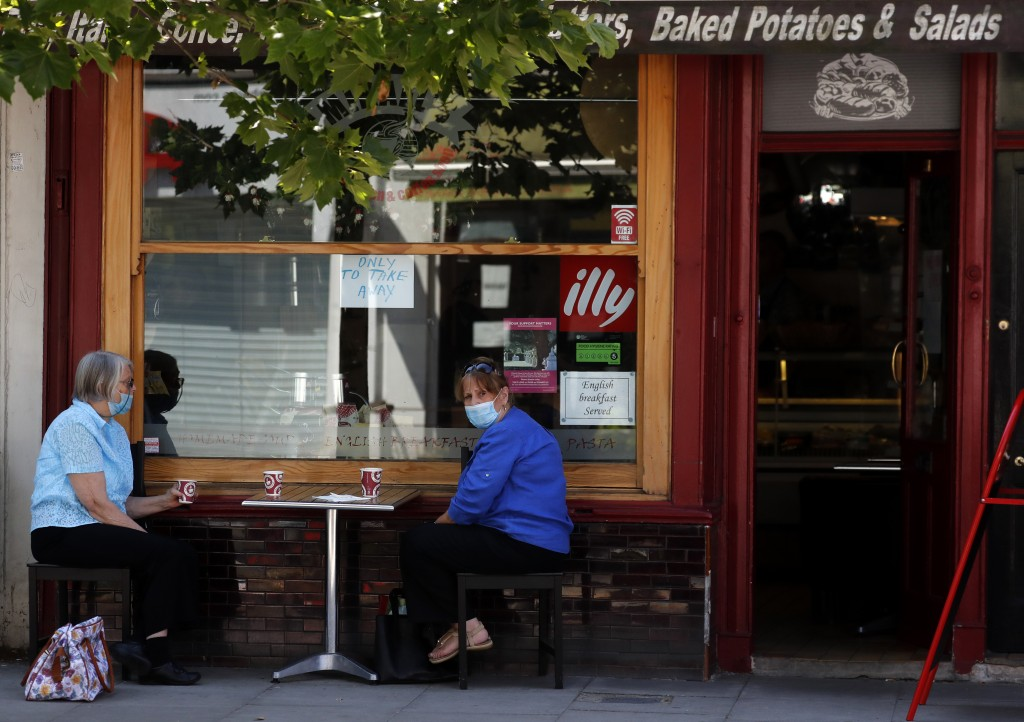 Two women sit outside a take away only coffee shop in London, Tuesday, June 23, 2020. The closing of restaurants, hair cutters and pubs will be under ...