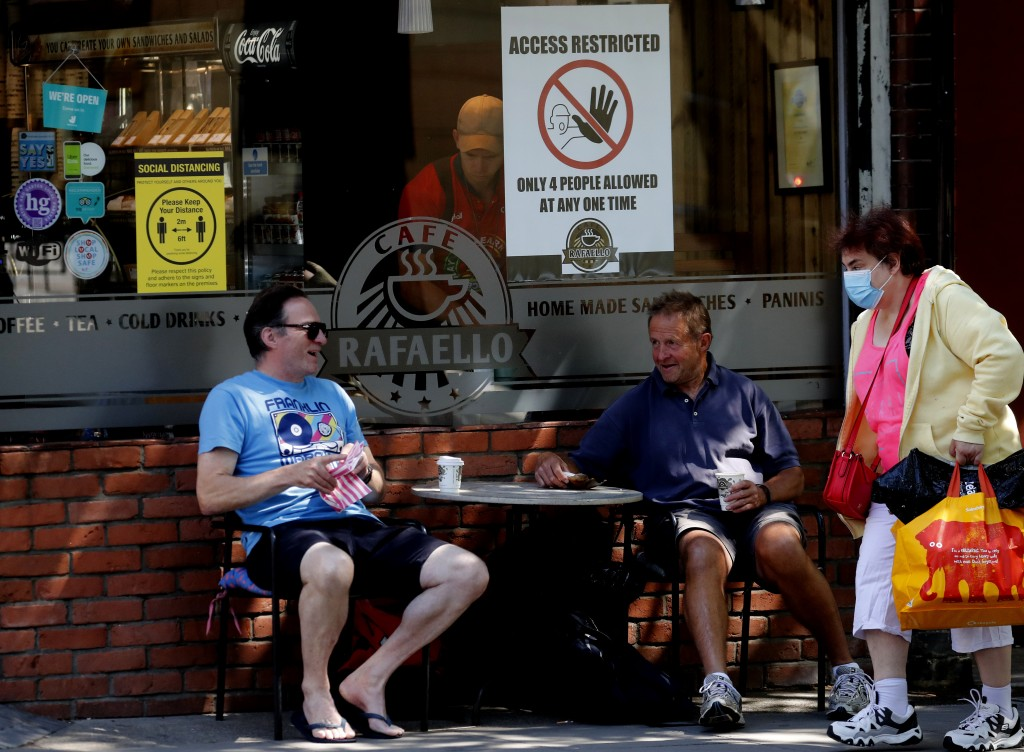 People sit outside at a restaurant currently only doing take away food in London, Tuesday, June 23, 2020. The closing of restaurants, hair cutters and...